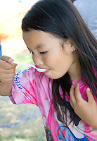 Hmong child age 11 enjoying a taste of the rich Hmong cuisine. Hmong Sports Festival McMurray Field St Paul Minnesota USA