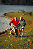 Senior couple biking at lake