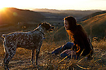 Kelli Ortmann-Pellegrini sits on a hillside at sundown with her dog Buck, at LP Ranch in San Benito, Calif.,  to enjoy the warm colors and the ending of a day, on a Friday. November 26, 2010.