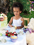 Happy smiling girl having a party outdoors sitting at the table and eating a cupcake
