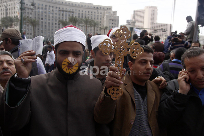 Opposition supporters hold Holy Quran and a cross in Tahrir Square in Cairo February 6, 2011. Demonstrators camped out in Cairo's Tahrir Square, which has become an epicentre for protest, vowed to intensify their battle to oust Egypt's President Hosni Mubarak but the 82-year-old president has said he will stay until September elections because the alternative is chaos.  Photo by Ahmed Asad