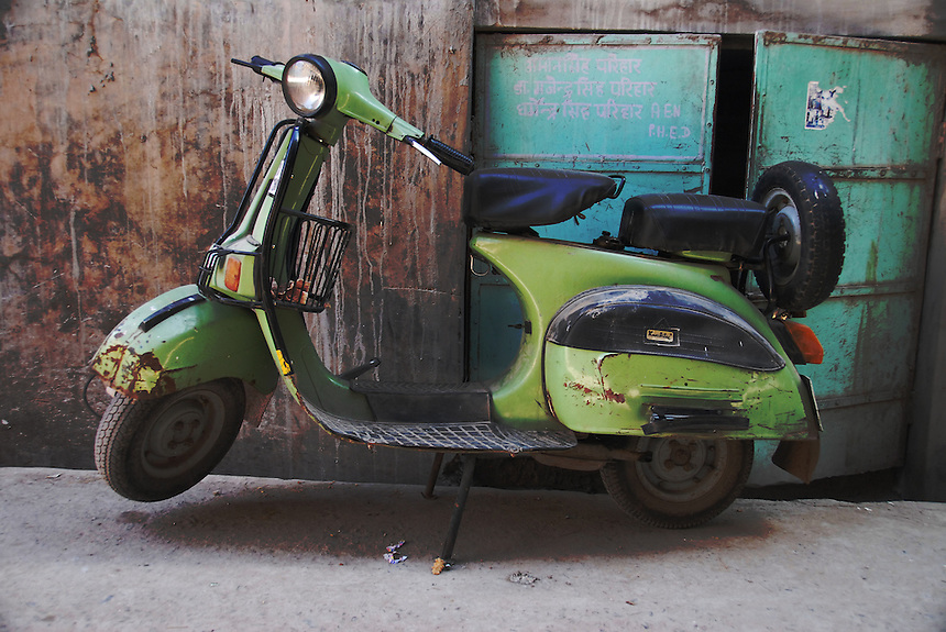A rusty scooter is parked on the edge of a narrow street in Jodhpur, Rajasthan's Blue City.