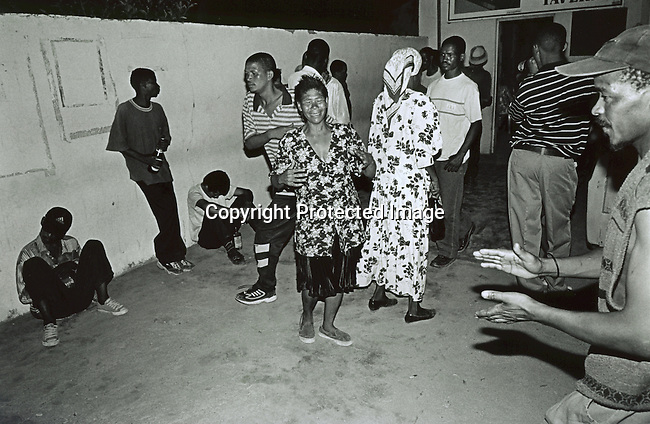 UPINGTON, SOUTH AFRICA - FEBRUARY 9: Unidentified drunk people dance in an illegal bar February 9, 2002 in Loisevale near Upington, South Africa. Loisevale is a poor and destitute black township where unemployment is high and a number of social problems exist including domestic violence and alcohol abuse. Baby Thsepang, an eight-month old baby, was raped by her father in a house on this street in October 2001. The baby rape shocked the country. South Africa is struggling with an increasing number of rapes and sexual abuse of young children. In addition, the country has the highest number of rapes in the world. (Photo by Per-Anders Pettersson)
