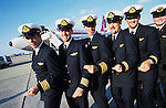 """John Travolta, captain and pilot, of his own jumbo jet, snaps his fingers as he and his crew play a scene from 'Saturday Night Fever' with his plane behind...John Travolta is pilot of his very own jumbo jet, a 1964 Boeing 707-100 series. In 2003, John Travolta flew his jumbo jet around the world, in partnership with Quantas, to rekindle confidence in commercial aviation, and to remind us that elegance and style are a part of flying. The crew are dressed in tailor made authentic uniforms from the Quantas museum. The men's uniforms are styled on British Naval uniforms and the ladies' designed by Chanel. His jumbo jet sports a personalised number plate N707JT which speaks for itself. The aircraft is named """"Jett Clipper Ella"""" dedicated to his son and daughter. This jumbo together with his other aircraft are housed in purpose built hangars at his home in Florida, USA."""