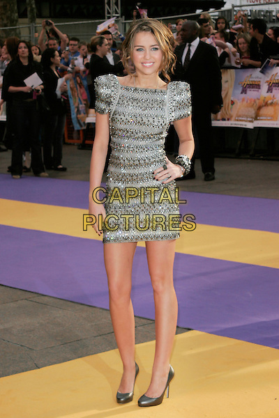 "MILEY CYRUS .UK Premiere of ""Hannah Montana: The Movie"" at the Odeon Leicester Square, London, England. .April 23rd 2009 .full length silver grey gray beaded beads embellished jewel encrusted dress shoulder pads structured shoulders sculpted shoes bracelets bangles hand on hip.CAP/AH.©Adam Houghton/Capital Pictures."