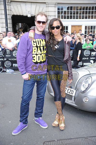 MAXIMILLION COOPER & EVE (Eve Jihan Jeffers) .The 2010 Gumball 3000 Rally, London, England..May 1st, 2010.full length black jacket trousers wedges shoes sunglasses shades leather leggings leopard print brown gold wedges jeans denim purple top yellow.CAP/DS.©Dudley Smith/Capital Pictures