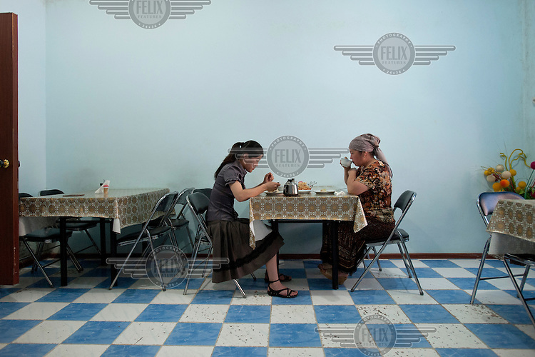 Two women eat and drink at a cafe.