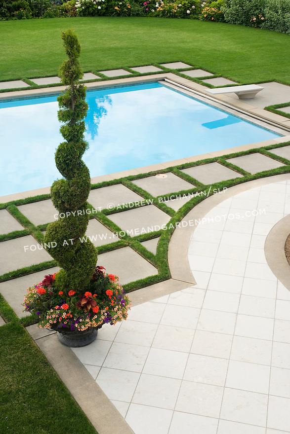 An overhead view looking down on half of a beautifully manicured, poolside landscape featuring lush green grass lawn, a border of mixed annuals, perennials and grasses, a beautiful blue swimming pool with diving board, a geometric pattern of concrete pavers and wide grass edging strips to set off the pool, and a dramatic pot of curly evergreen topiary and summer annuals in this Northwest summer scene in a suburban community east of Seattle.
