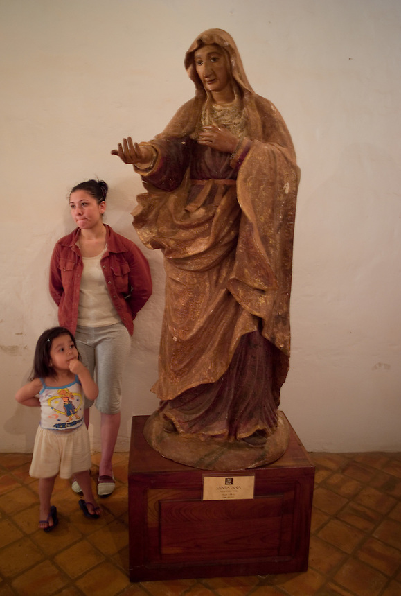 Irma Ramirez and Lelis Martinez, 3, wife and daughter of museum caretaker Isabelino Martinez, stand next to a statue of Saint Anne at a religious art museum in the former mission town of Santa Maria de Fé (acute accent on the e in Fe), Paraguay. Scores of Jesuit missions in the area where Paraguay, Argentina and Brazil meet were built in the 17th century and abandoned when the Jesuits were expelled in the 18th century. Ruins of some of these missions still haunt hilltops in the region. (Kevin Moloney for the New York Times)