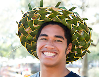 A smiling young Hawaiian man wearing a hat handwoven from lauhala (pandanus leaves), Hawai'i.