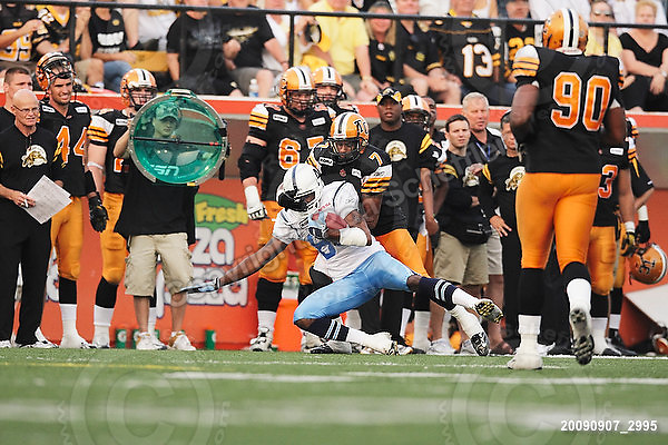 September 7, 2009; Hamilton, ON, CAN; Hamilton Tiger-Cats defensive back Bo Smith (7) tackles Toronto Argonauts wide receiver Chad Lucas (84). CFL football - the Labour Day Classic - Toronto Argonauts vs. Hamilton Tiger-Cats at Ivor Wynne Stadium. The Tiger-Cats defeated the Argos 34-15. Mandatory Credit: Ron Scheffler.