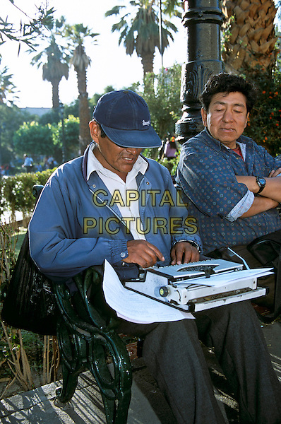 Man typing on portable typewriter for payment, Plaza de Armas, Arequipa, Peru