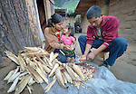 Jovita Guzman, a Maya Mam woman, pulls the grain off of corn at her home in Comitancillo, Guatemala, with help from her husband Maximilian Porfirio Garcia. Their two-year old daughter Marilisa accompanies them.