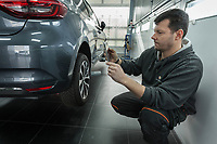 """Switzerland. Canton Geneva. Plan-les-Ouates. Renault Retail Group, RRG Suisse. """"Spot-repair"""" by Dells Angels. Renault Clio car inside a paint booth in auto body repair garage. A worker takes a picture with an iPad. 4.03.2020 © 2020 Didier Ruef"""