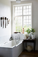 A light, bright bathroom with a small wooden table, laden with vases of flowers, sits in front of a large window. Vintage wooden spoons hang on the wall above the bath.