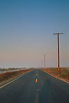 Telephone Poles along empty rural two lane country road at sunrise in the Delta, near Stockton, San Joaquin County, California
