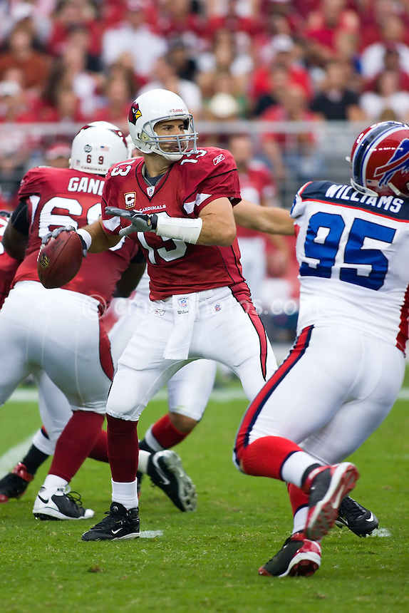 Oct 5, 2008; Glendale, AZ, USA; Arizona Cardinals quarterback Kurt Warner (13) drops back to pass while Buffalo Bills defensive tackle Kyle Williams (95) applies pressure in the first quarter of a game at University of Phoenix Stadium.