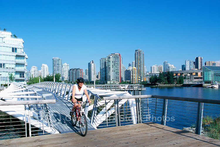 Vancouver, BC, British Columbia, Canada - Cyclist cycling on Pedestrian Bridge at Village on False Creek (aka Olympic Village)