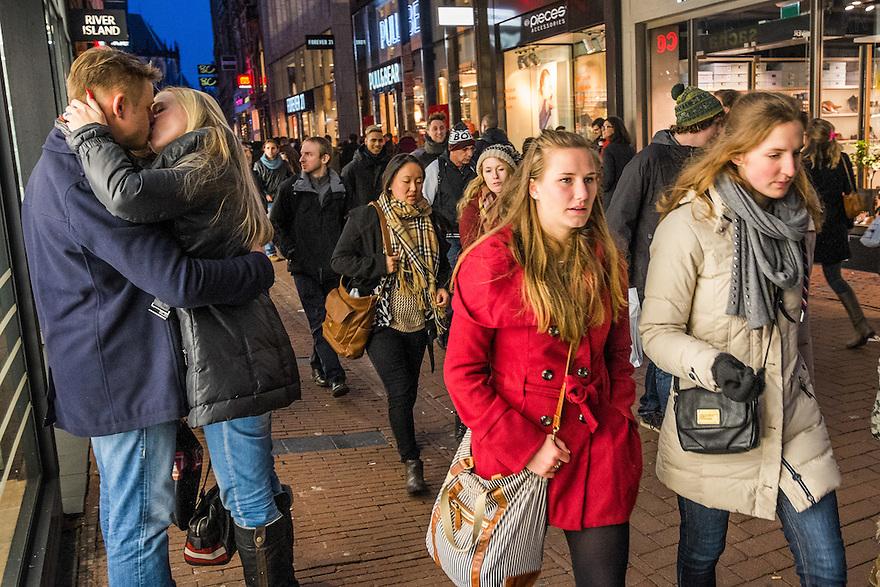 Nederland, Amsterdam, 31 jan 2015<br /> Winkelend publiek in het centrum van de stad, Kalverstraat. Een stelletje kust na het doen van aankopen.<br /> Foto: (c) Michiel Wijnbergh