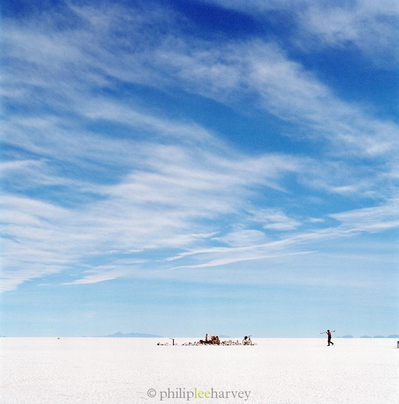 Miner walking on Salar de Uyuni salt flats, Bolivia. The Salar de Uyuni are the worlds largest salt flats.