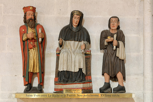 St Yves between rich and poor men, polychrome wood sculpture, 16th century, in Quimper Cathedral, or the Cathedrale Saint-Corentin de Quimper, a Gothic Roman Catholic cathedral founded in 1239 and completed in the 15th century, in Quimper, Finistere, Brittany, France. St Yves was a 13th century saint and patron saint of Brittany. The cathedral is listed as a national monument. Picture by Manuel Cohen