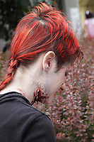 female participant in the prague event zombie walk in may 2014. Photographed in profile,showing part of the make up scars on her neck. Female having red hair.