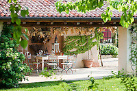 An al fresco dining area under the porch with a terracotta tiled roof