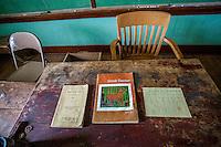 Teacher's desk w/ school book & student's number worksheet in classroom of old abandoned school in Boyes, MT