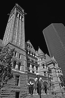 Looking up at Toronto Old City Hall in black and white with the impact of the newer glass tower in the background.