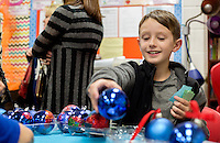 STAFF PHOTO JASON IVESTER --12/09/2014--<br /> Daxton Evans, Shaw Elementary fourth-grader, displays his glitter ornaments at his booth on Tuesday, Dec. 9, 2014, during the Springdale school's Christmas Bazaar. Students came up with business ideas, implemented them and sold their products at the event. They also rented booth spaces to local businesses to help fund their products. Students split money from the sale to the Northwest Arkansas Children's Shelter and to the the Springdale Animal Shelter.