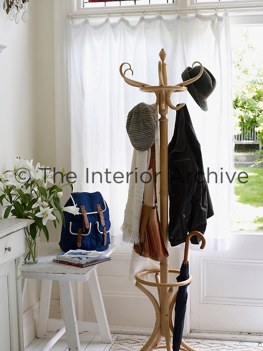 Interior shows a wooden hat stand in front of a window. A white, wooden drawer and chair are beside with a blue ruck sack and a vase of white lilies. The hat stand has coats, a scarf and a tall umbrella. Styling by Alice King.