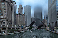 The lift bridges on the Chicago River allow a group of sailboats to make their way to Lake Michigan on a foggy morning.
