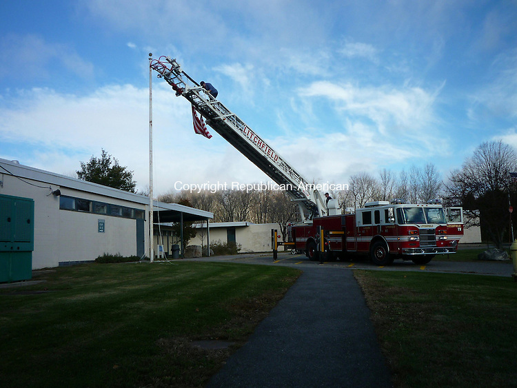 LITCHFIELD, CT - 9 November, 2010 - 110910BR01 - Litchfield volunteer firefighters dispatched the town's ladder truck to Bantam Court Tuesday to help untangle the halyard and rescue a stranded flag. Brigitte Ruthman Republican-American.
