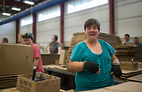 NWA Democrat-Gazette/Charlie Kaijo Kacey Anderson of Pea Ridge laughs with friends while inspecting used Walmart boxes to be reused or recycled on Monday, October 9, 2017 at Open Avenues in Rogers. Many of clients develop close relationships with one another. The organization partners with 22 different businesses and provides job and life skills training to people with disabilities, currently serving 110 clients. The clients work on projects at work stations and are paid for their work. This year they have focused on transitioning their clients into jobs in the community, many with Walmart, Zaxbys and Harp's.