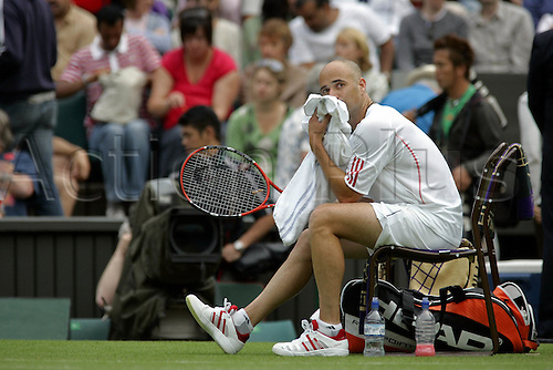 27 June 2006: American player Andre Agassi sitting with a towel during his first round men's singles match against Pashanski on the second day at the All England Lawn Tennis Championships, Wimbledon, London. Agassi won 2-6 6-2 6-4 6-3 Photo: Glyn Kirk/Actionplus...060627 man men rest