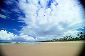 Bahia State, Brazil. Unspoilt wide, sandy, palm fringed beach on the Costa Verde with young couple walking.