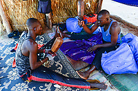 BURKINA FASO , Bobo Dioulasso, craftsman making the traditional garment Boubou for men from damask fabric, tap with a wooden hammer on the fabric that it becomes hart and glossy