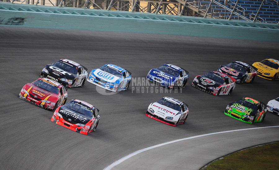 Nov. 20, 2010; Homestead, FL, USA; NASCAR Nationwide Series driver Kyle Busch (18) races alongside teammate Joey Logano (20) during the Ford 300 at Homestead Miami Speedway. Mandatory Credit: Mark J. Rebilas-