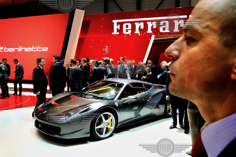 Invited guests and major dealers gather around the Ferrari stand during the launch of new models at the Geneva Motor Show.