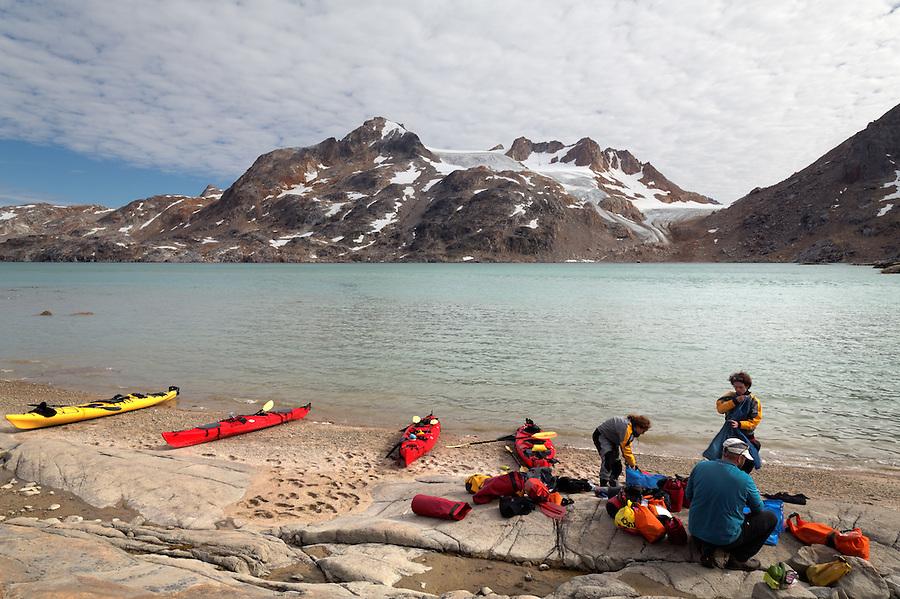 Sea kayakers unloading sea kayaks on beach, Sammileq Fjord, Ammassalik Island, East Greenland
