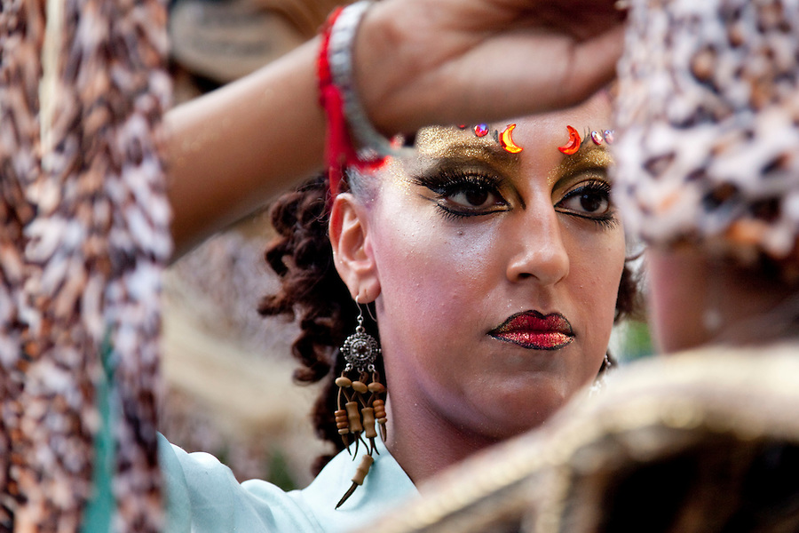 A womans applys makeup in preparation for the parade of Llamadas in Montevideo.  One of the most imporant elements of Carnaval in Uruguay is Candombe, an African drum rhythm played on tambor drums.  It was revitalized in the Americas by black slave descendents as a way by which to reclaim their cultural heritage and battle for civil rights.