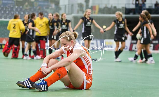 LEIPZIG -  Teleurstelling bij Vera Vorstenbosch terwijl de Duitse dames feestvieren  , zaterdag na de halve finalewedstrijd bij de vrouwen tussen Nederland en Duitsland (1-4) bij het EK Zaalhockey in Leipzig.  Duitsland plaatst zich voor de finale. ANP KOEN SUYK