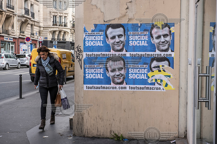 A woman walks past posters pasted onto a wall in Paris campaigning against the presidential hopeful Emmanuel Macron during the 2017 presidential election campaign.