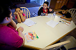 Sophia Sawyer, left, helps her children, from left, Frances, Isaiah, and Daniel, with their homework January 27, 2010 in Sacramento, Calif. The Sawyer family receives $540/month in CalWORKs assistance from the state of California. Dennis is currently unable to work while recovering from cancer, and Sophia hasn't been able to find work. Gov. Arnold Schwarzenegger has proposed eliminating the CalWORKs program in an effort to balance the state's budget. CREDIT: Max Whittaker for The Wall Street Journal.CABUDGET