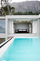 The master bedroom seen from across the pool. Huge sliding doors that disappear into the wall either side when open mean it's also possible to jump straight into the pool from the bedroom itself.
