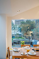 An Andoo kitchen table by Walter Knoll is laid for lunch in the new extension with a view of the patio garden