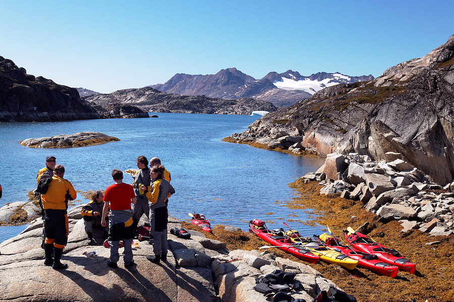 Sea kayakers taking break on beach, Sammileq Fjord, Ammassalik Island, East Greenland