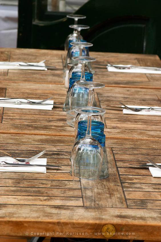 Le Bistrot des Alpilles restaurant. A row of tables prepared for lunch with upside down wine and water glasses knifes and forks cutlery and napkins on the wooden surface. Saint Remy Rémy de Provence, Bouches du Rhone, France, Europe