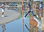Laquesha Jackson, Annapolis, leaps from the sidewalk over water  on Dock St. after an unusually high tide floods the road.