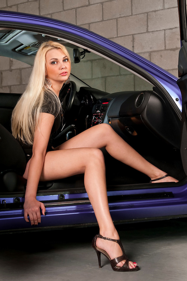 Sensual blond girl getting out of a car in a garage